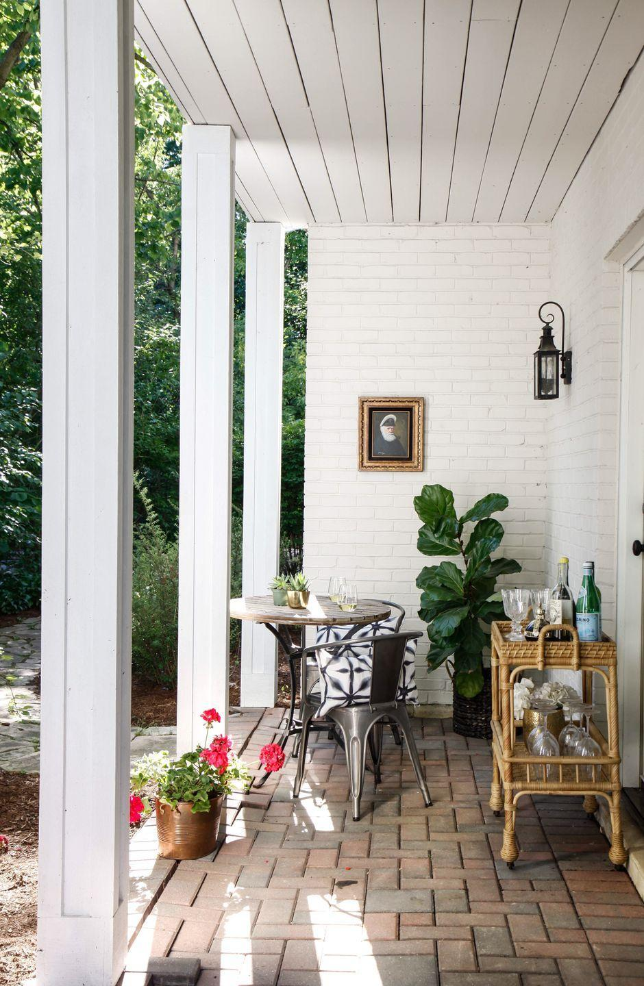 """<p>""""A bar cart is a simple yet impactful way to transform a patio into an outdoor cocktail room,"""" Christina Samatas and Renee DiSanto of <a href=""""http://parkandoak.com/"""" rel=""""nofollow noopener"""" target=""""_blank"""" data-ylk=""""slk:Park & Oak"""" class=""""link rapid-noclick-resp"""">Park & Oak</a> tell us. """"For this space, we centered the porch around a rattan bar cart for a touch of vintage character that uniquely contrasts against the brick and paneled ceiling. We always like to make any outdoor space feel like a continuation of the interior, so we chose artwork and decorative pillows that would create a sense of cohesiveness with the rest of the home. To carry the garden up to the porch, we added a few potted plants and flowers, elevated with a rustic copper pot and woven basket. The mixture of rustic and sophisticated elements comes together to create a timeless and functional outdoor space fit for enjoying cocktails alfresco.""""</p>"""