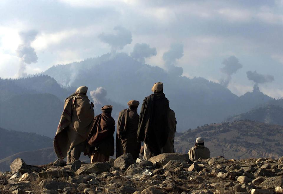 Image: AFGHAN FIGHTERS WATCH SEVERAL EXPLOSIONS FROM US BOMBINGS IN THE TORABORA MOUNTAINS. (Erik de Castro / Reuters file)