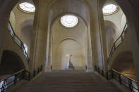 The Winged Victory of Samothrace sculpture stands at the top of a staircase in a deserted Louvre museum, in Paris, Thursday, Feb. 11, 2021. It's uncertain when the Louvre will reopen, after being closed on Oct. 30 in line with the French government's virus containment measures. But those lucky enough to get in benefit from a rarified private look of collections covering 9,000 years of human history -- with plenty of space to breathe. (AP Photo/Thibault Camus)