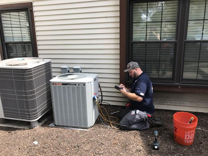 A service technician for Christian Heating and Air Conditioning of Upper Southampton checks out an air-conditioner function.