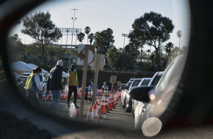 Health care workers are reflected in the rear view mirror of a vehicle as they prepare to distribute a COVID-19 vaccine to Los Angeles residents as they wait in line in their cars in the early morning at Dodger Stadium on Tuesday, Jan. 26, 2021, in Los Angeles. California is revamping its vaccine delivery system to give the state more control over who gets the shots following intense criticism of a slow and scattered rollout by counties. (AP Photo/Richard Vogel)