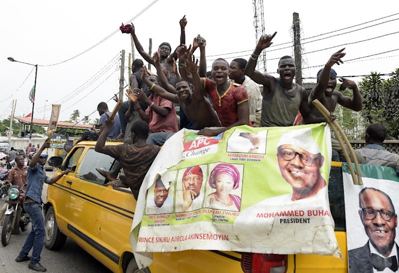Supporters of newly-elected Nigerian President Muhammadu Buhari sit on top of a bus as they celebrate the victory their candidate in Lagos on April 1, 2015