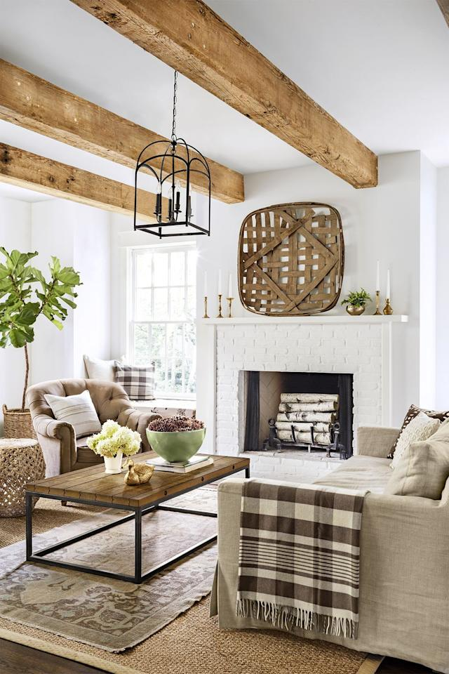 <p>Large wooden beams make an all-white room cozy enough for late night hangs. Tie in baskets and mantel decorations in a similar wood type and finish.</p>