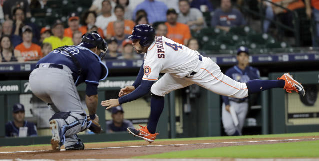 Houston Astros' George Springer (4) dives toward home plate as Tampa Bay Rays catcher Wilson Ramos (40) reaches to tag him during the first inning of a baseball game Tuesday, June 19, 2018, in Houston. Springer was out on play. (AP Photo/David J. Phillip)