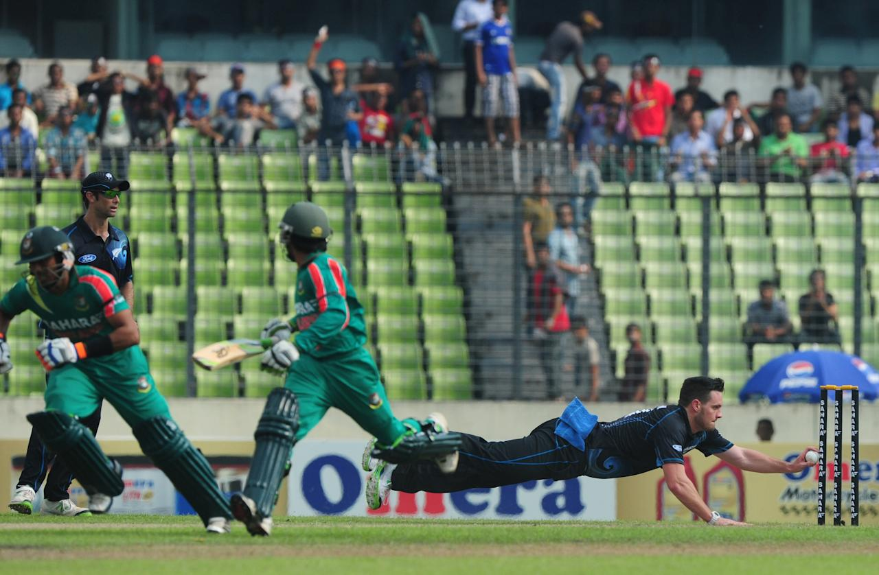 New Zealand cricketer Mitchell McClenaghan (R) is watched by teammate Grant Elliott (L) as he breaks the stumps while Bangladesh batsmen Anamul Haque (L) and Mominul Haque (2R) try to make their ground during the first one-day-international (ODI) cricket match between Bangladesh and New Zealand at Sher-e Bangla National Stadium in Dhaka on October 29, 2013 . AFP PHOTO/ Munir uz ZAMAN        (Photo credit should read MUNIR UZ ZAMAN/AFP/Getty Images)