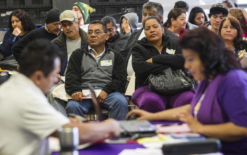 Applicants wait during a health care enrollment event at SEIU-UHW office, Monday, March 31, 2014, in Commerce, Calif. Monday marks this year's open enrollment deadline, but consumers will get extra time to finish their applications. (AP Photo/Ringo H.W. Chiu)