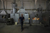 A glass-worker works at a glass artistic creation as he walks past methane powered ovens in a factory in Murano island, Venice, Italy, Thursday, Oct. 7, 2021. The glassblowers of Murano have survived plagues and pandemics and have transitioned to highly prized artistic creations to outrun competition from Asia, but surging energy prices may be their doom. (AP Photo/Antonio Calanni)