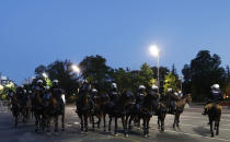 Serbian police on horses guard the area during clashes with protesters in Belgrade, Serbia, Wednesday, July 8, 2020. Serbia's president Aleksandar Vucic backtracked Wednesday on his plans to reinstate a coronavirus lockdown in Belgrade after thousands protested the move and violently clashed with the police in the capital. (AP Photo/Darko Vojinovic)