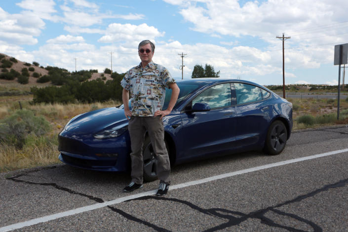 Howard Coe poses in front of his wife's Tesla sedan on Tuesday, Sept. 14, 2021, on a road near Nambé Pueblo outside of Santa Fe, N.M. Coe welcomed the opening of a new Tesla store and repair shop where he can pickup an SUV he's buying. Last year, he and his wife had to pick up her car in Denver, Colo., about five hours away, because of New Mexico laws that bar companies like Tesla from selling cars directly to customers. (AP Photo/Cedar Attanasio)
