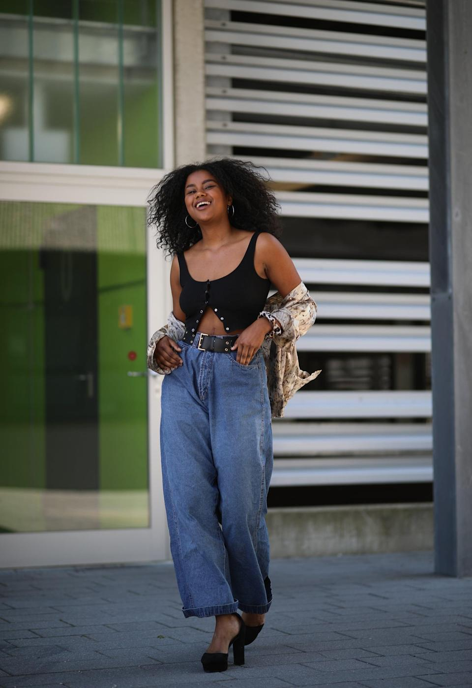 <p>Cinch the waist of your baggy jeans and dress 'em up with platforms and a crop top. </p>