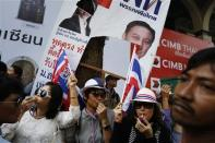 Under a damaged pre-election poster of Thai Prime Minister Yingluck Shinawatra, anti-government protesters blow whistles as they greet fellow demonstrators marching through Bangkok's financial district January 21, 2014. REUTERS/Damir Sagolj