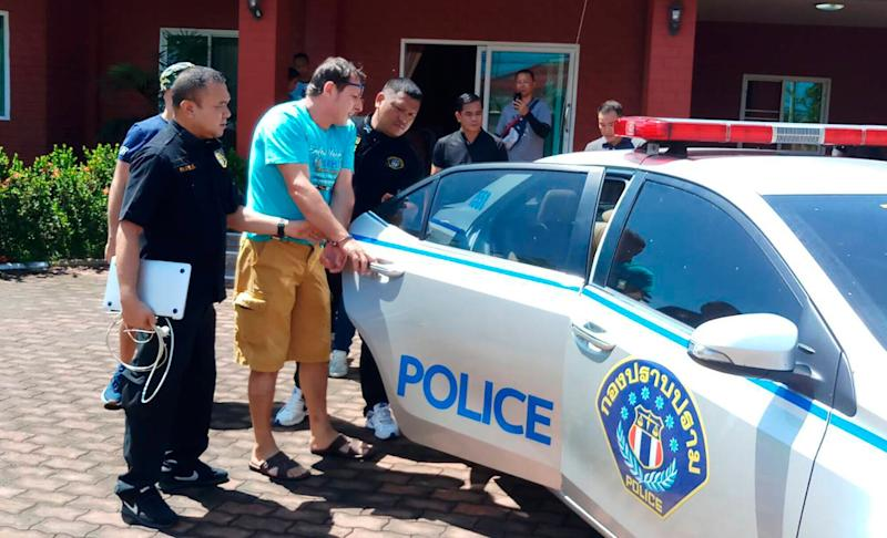 Italian Francesco Galdeli, in handcuffs, was arrested by Thai police officers at a house in Chonburi