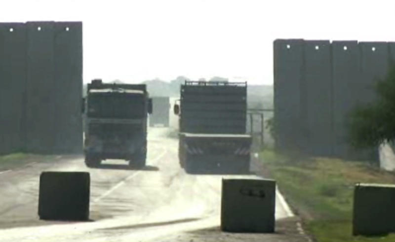 In this frame grab taken from AP video, trucks pass through the Kerem Shalom Crossing at the border of Israel and the southern Gaza Strip Monday, Dec. 31, 2012. Israel has started allowing long-banned building materials into the Gaza Strip, its first key concession to the territory's Hamas rulers under a cease-fire that ended eight days of intense fighting in November, the military said Monday. (AP Photos/APTN)