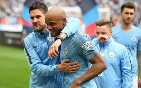 Vincent Kompany is embraced by his Manchester City team-mates - Credit: afp