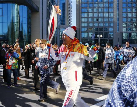 United Nations Secretary-General Ban Ki-moon runs with the 2014 Sochi Olympics torch as the torch relay arrives in Sochi February 6, 2014. REUTERS/Shamil Zhumatov