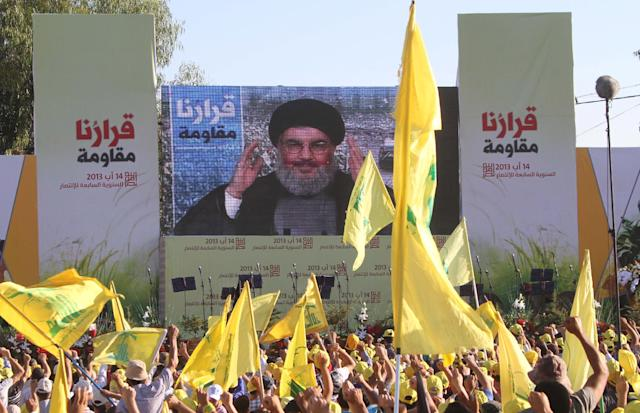 """Hezbollah supporters raise their hands to great Hezbollah leader Sheik Hassan Nasrallah, who delivers a speech through a giant TV screen from a secret location, during a rally marking the seventh anniversary of the 2006 Israel-Hezbollah war, at the southern Lebanese-Israel border village of Aita, Lebanon, Friday Aug. 16, 2013. Sheik Hassan Nasrallah says all preliminary investigations show Takfiri groups, a term for Sunni radicals, were likely behind Thursday's bombing in a predominantly Shiite southern suburb of Beirut that killed tens of people and wounded hundreds. The Arabic words on the left and right read:""""Our decision is resistance."""" (AP Photo/Mohammed Zaatari)"""