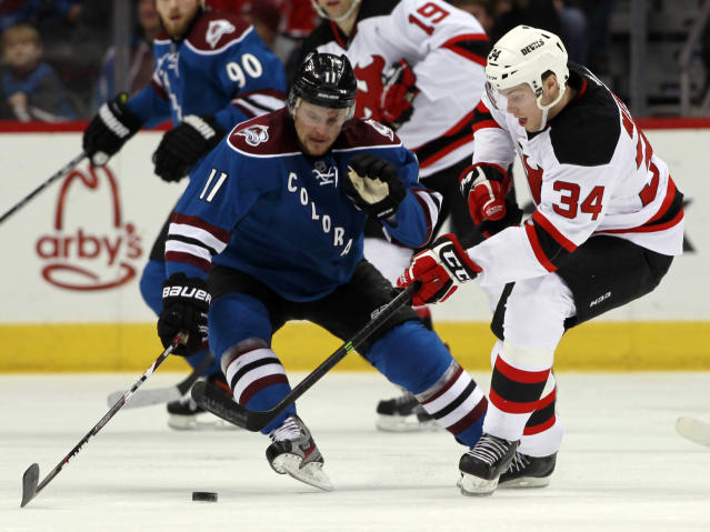 Colorado Avalanche left wing Jamie McGinn, left, fights for control of the puck with New Jersey Devils defenseman Jon Merrill in the second period of an NHL hockey game in Denver, Thursday, Jan. 16, 2014. (AP Photo/David Zalubowski)