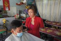 Le Thi Kim Tram, who lost her left arm in a traffic accident, works at her barbershop in Ho Chi Minh City