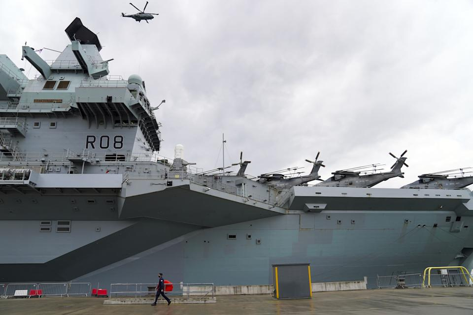 A Royal Navy Merlin helicopter lands on to HMS Queen Elizabeth at HM Naval Base, Portsmouth, ahead of the ship's maiden deployment to lead the UK Carrier Strike Group on a 28-week operational deployment travelling over 26,000 nautical miles from the Mediterranean to the Philippine Sea. Picture date: Saturday May 22, 2021. (Photo by Steve Parsons/PA Images via Getty Images)