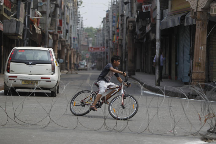 """An Indian boy rides a bicycle past a barbed wire erected as part of security restrictions in Jammu, India, Tuesday, Aug.6, 2019. India's lower house of Parliament was set to ratify a bill Tuesday that would downgrade the governance of India-administered, Muslim-majority Kashmir amid an indefinite security lockdown in the disputed Himalayan region. The Hindu nationalist-led government of Prime Minister Narendra Modi moved the """"Jammu and Kashmir Reorganization Bill"""" for a vote by the Lok Sahba a day after the measure was introduced alongside a presidential order dissolving a constitutional provision that gave Kashmiris exclusive, hereditary rights. (AP Photo/Channi Anand)"""