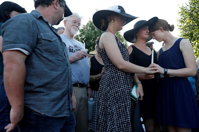 <p>Three daughters of Wendi Winters, Winters, Summerleigh and Montana Geimer hold each other at right as Capital staffers Paul Gillespie, (L) and Pat Furgurson stand nearby during a candlelight vigil held near the Capital Gazette, the day after a gunman killed five people (including Wendi Winters) inside the newspaper's building in Annapolis, Md., June 29, 2018. (Photo: Leah Millis/Reuters) </p>