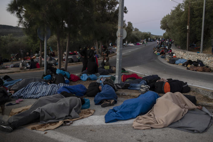 FILE - In this Thursday, Sept. 10, 2020, file photo, refugees and migrants sleep on a street near the destroyed Moria camp following a fire, on Lesbos island, Greece. Greece's notoriously squalid refugee camp of Moria burnt down last September on the island of Lesbos. It left around 12,000 people in need of emergency housing as winter approached. European leaders then vowed such squalid facilities would be a thing of the past. But aid agencies say that a year later the conditions for asylum seekers on the eastern Greek islands have barely improved. (AP Photo/Petros Giannakouris, File)