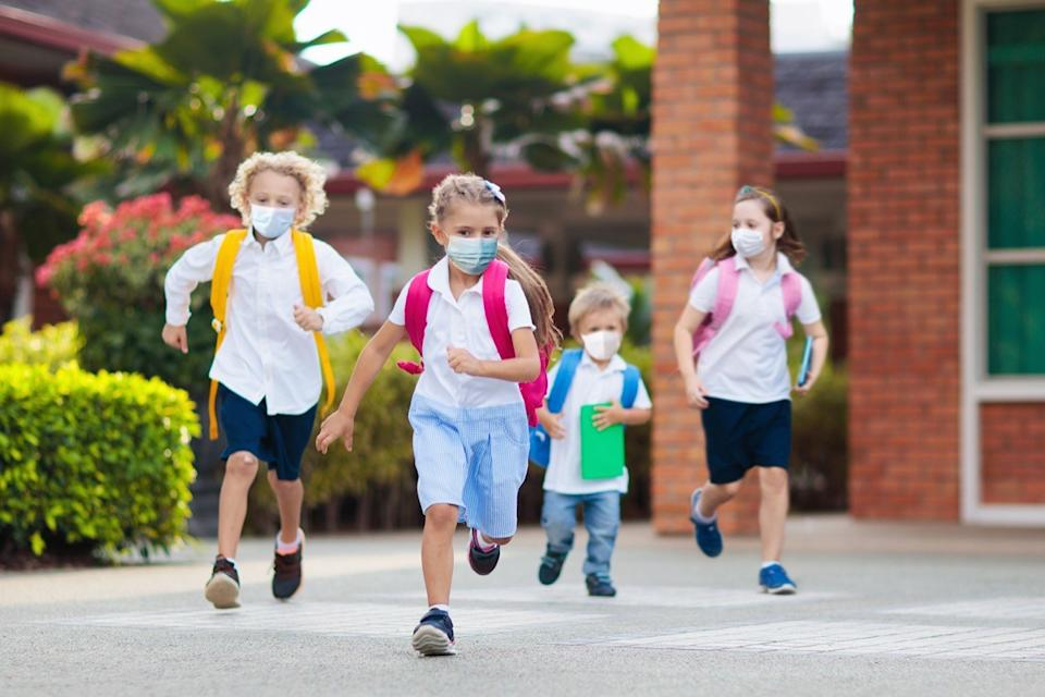 Kids in masks running through school yard