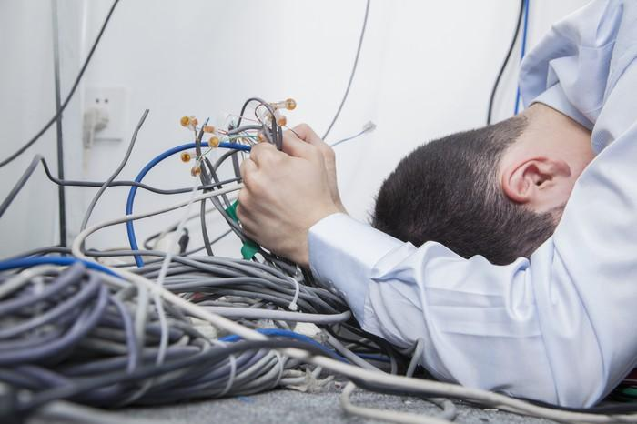 Grasping a mess of ethernet cables, a young man hides his head behind his left arm.