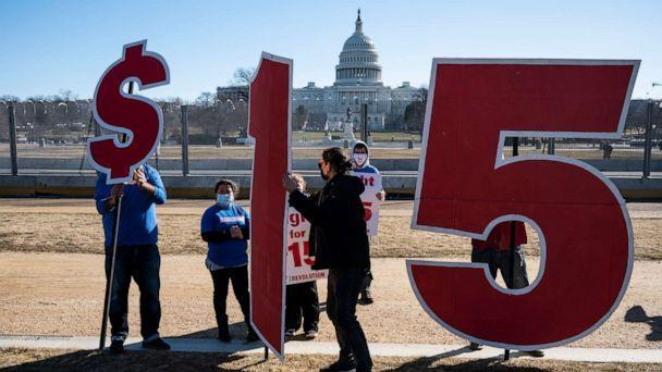 PHOTO: Activists hold signs outside the Capitol complex in Washington on Feb. 25, 2021, to call on Congress to pass the $15 federal minimum wage hike proposed as part of the COVID relief bill. (Bill Clark/CQ-Roll Call via Getty Images, FILE)