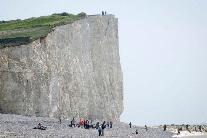 Tourists continue to hang dangerously close to the edge of the cliff despite warnings. Source: Yahoo
