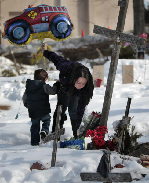 Dina DeMaio, of North Dartmouth, Mass., places flowers at a makeshift memorial to her brother Thomas Marion, as her son Logan, left, accompanies her at the site of The Station nightclub fire in West Warwick, R.I., Wednesday, Feb. 20, 2013. Marion was one of 100 people killed in the Feb. 20, 2003 fire that started when pyrotechnics for the hard rock band Great White ignited flammable foam that had been installed as soundproofing. (AP Photo/Steven Senne)