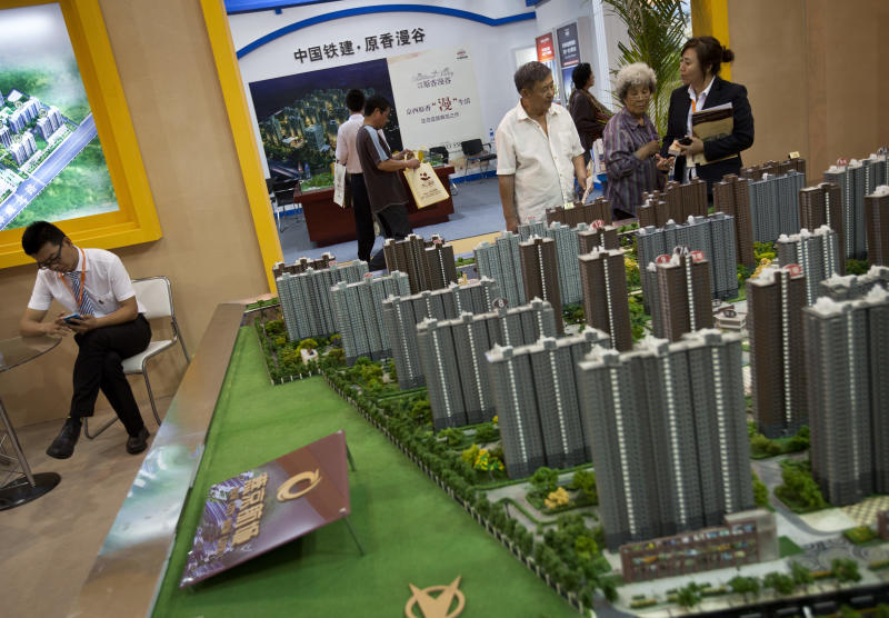 FILE - In this Sept. 21, 2012 file photo, an elderly Chinese couple look at a model of a property on sale during the China Property and Investment Show in Beijing. China's economic growth has fallen to a 3 1/2 year low but retail sales and investment improved in a possible sign the slowdown is stabilizing. The government said Thursday, Oct. 18, 2012 economic output grew 7.4 percent in the three months ending in September. That is a decline from the previous quarter's 7.6 percent and the lowest level since the first quarter of 2009. (AP Photo/Andy Wong, File)