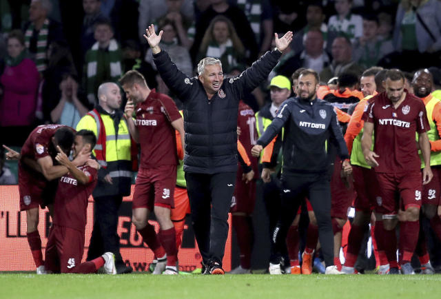 Cluj's manager Dan Petrescu, centre, celebrates victory after the final whistle of the Champions League third qualifying round second leg soccer match between Celtic and CFR Cluj, at Celtic Park, in Glasgow, Scotland, Tuesday, Aug. 13, 2019. (Jane Barlow/PA via AP)