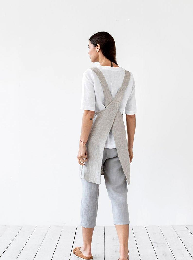 """<p>The only thing better than a lightweight apron is an option that feels like you're not wearing a protective covering at all. This pinafore-style linen option boasts a chic cross-back design that allows you to put it on and take it off with ease—<a href=""""https://www.marthastewart.com/269923/chefs-apron"""" rel=""""nofollow noopener"""" target=""""_blank"""" data-ylk=""""slk:no strings or ties necessary"""" class=""""link rapid-noclick-resp"""">no strings or ties necessary</a>.</p> <p><strong><em>Shop Now: </em></strong><em>MagicLinen Pinafore Linen Apron, $54, <a href=""""http://www.awin1.com/cread.php?awinmid=6220&awinaffid=272513&clickref=MSL12StylishApronsThatHaveYouCoveredintheKitchensmeyerKitGal7844953202007I&p=https%3A%2F%2Fwww.etsy.com%2Flisting%2F597312194%2Fpinafore-linen-apron-japanese-cross-back%3F"""" rel=""""nofollow noopener"""" target=""""_blank"""" data-ylk=""""slk:etsy.com"""" class=""""link rapid-noclick-resp"""">etsy.com</a></em><em>.</em></p>"""