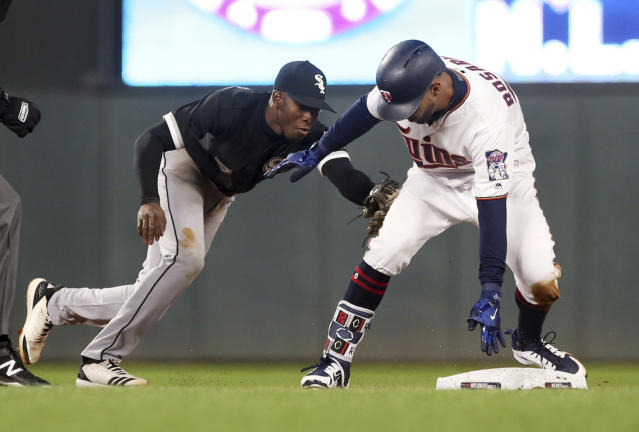 Minnesota Twins' Eddie Rosario beats the tag by Chicago White Sox shortstop Tim Anderson to double in the sixth inning of a baseball game Thursday, April 12, 2018, in Minneapolis. (AP Photo/Jim Mone)