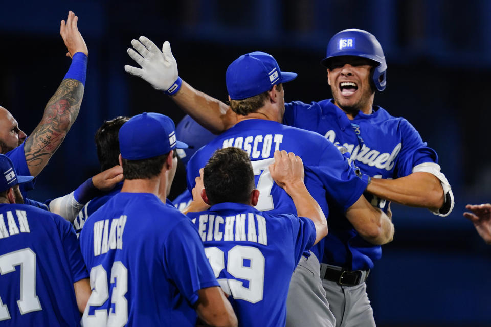 Israel's Danny Valencia, right, celebrate with teammates after hitting a two run home run during the eight inning of a baseball game against the Dominican Republicat at the 2020 Summer Olympics, Tuesday, Aug. 3, 2021, in Yokohama, Japan. (AP Photo/Matt Slocum)