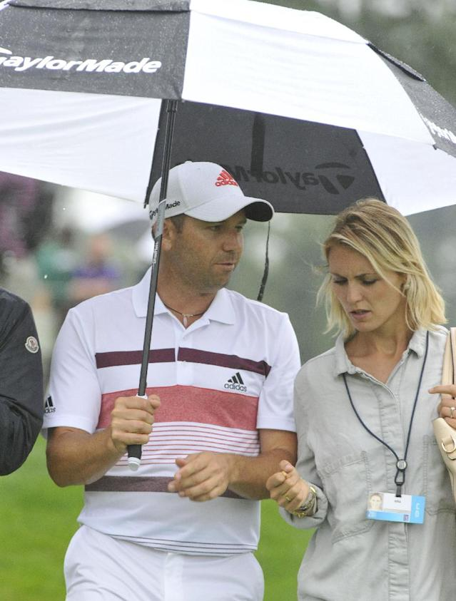 Sergio Garcia, walks off the 16th tee with his girlfriend Katharina Boehm, at the start of a rain delay, during the third round of the Bridgestone Invitational golf tournament, Saturday Aug. 2, 2014, in Akron, Ohio. (AP Photo/Phil Long)