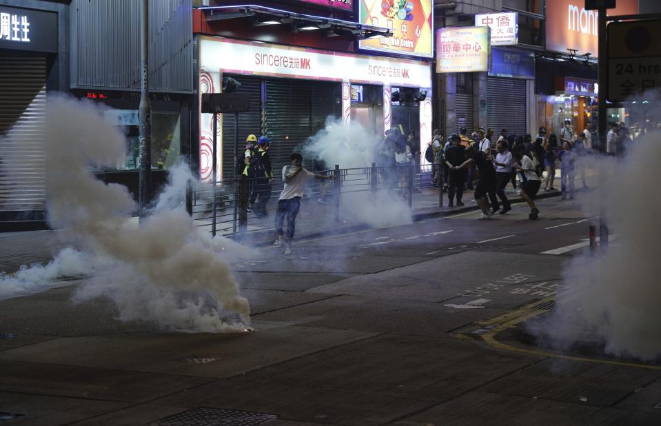 "Tear gas engulf the streets of Hong Kong on Sunday, Oct. 27, 2019. Hong Kong police fired tear gas Sunday to disperse a rally called over concerns about police conduct in monthslong pro-democracy demonstrations, with protesters cursing the officers and calling them ""gangster cops."" (AP Photo/Kin Cheung)"