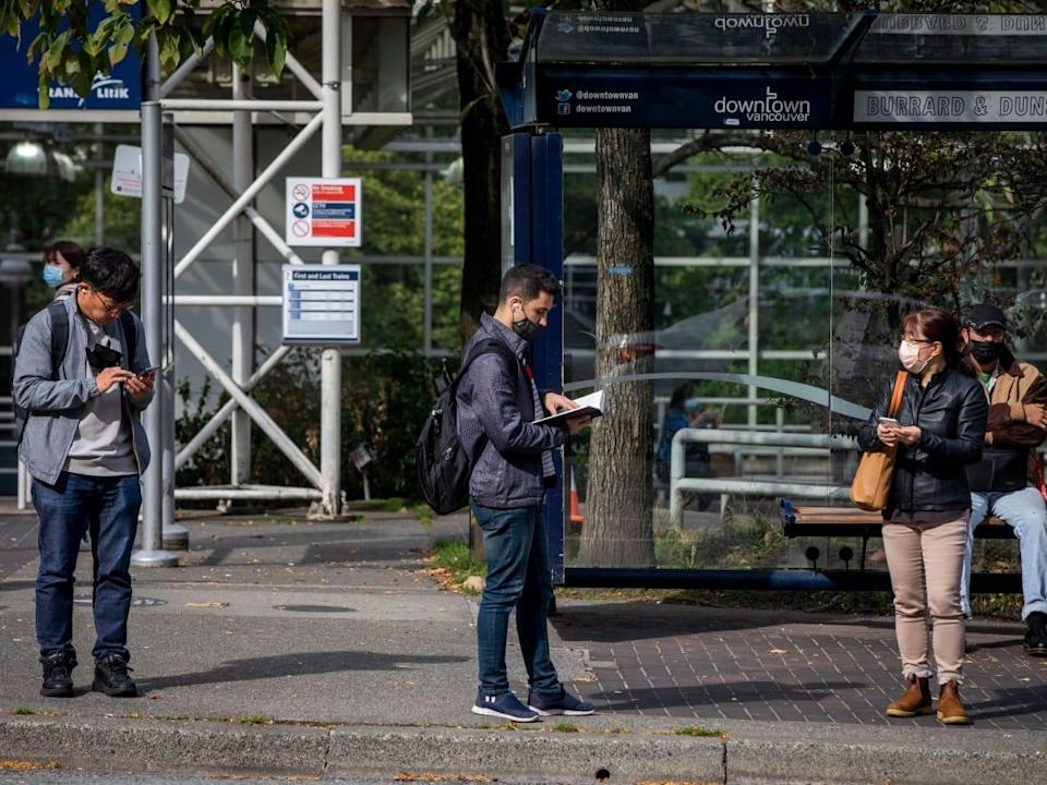 People wear protective face masks while waiting for a bus in downtown Vancouver on Oct. 4.  (Ben Nelms/CBC - image credit)