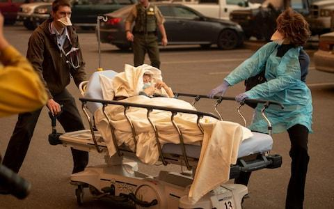 Patients are quickly evacuated from the Feather River Hospital as it burns down during the Camp fire in Paradise, California  - Credit:  JOSH EDELSON/AFP