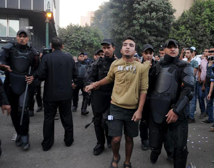Egyptian police arrest a protester in Cairo, Tuesday, Nov. 26, 2013, after they fired water cannons to disperse two protests by dozens of secular anti-government activists, the security forces' first implementation of a controversial new law forbidding protests held without a permit from authorities. (AP Photo/Mohammed Asad)