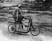 <p>A woman with her foot kicked over the handlebars sits atop a stationary scooter.</p>
