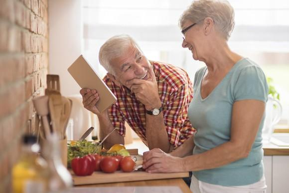 Senior man holding a notepad and smiling up at a senior woman while standing in a kitchen as she's cutting vegetables