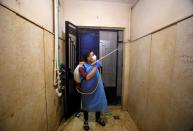 FILE PHOTO: A volunteer of a medical team sprays disinfectant in a house as a precaution to contain the spread of the coronavirus disease (COVID-19) at Shubra El Kheima in Al Qalyubia
