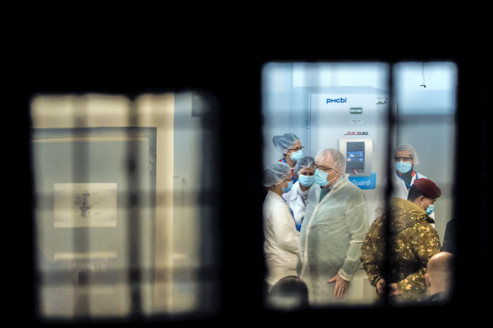 In this photo taken on Saturday, Dec. 26, 2020 medical staff and military personnel, wearing masks to protect against coronavirus, wait in the refrigerators room for the arrival of the first batch of COVID-19 vaccines at the National Center for Storage of the COVID-19 Vaccine, a military run facility, in Bucharest, Romania. Across the Balkans and the rest of the nations in the southeastern corner of Europe, a vaccination campaign against the coronavirus is overshadowed by heated political debates or conspiracy theories that threaten to thwart the process. In countries like the Czech Republic, Serbia, Bosnia, Romania and Bulgaria, skeptics have ranged from former presidents to top athletes and doctors. Nations that once routinely went through mass inoculations under Communist leaders are deeply split over whether to take the vaccines at all. (AP Photo/Vadim Ghirda)