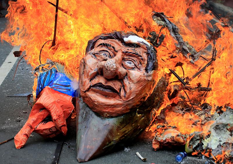Protesters burn an effigy of Philippine President Rodrigo Duterte to express their outrage while calling for the immediate pullout of U.S. troops in Mindanao province.