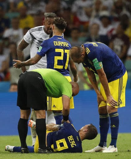 Referee Szymon Marciniak from Poland, bottom left, talks with Sweden's Marcus Berg, on the ground, as Germany's Jerome Boateng, top left, argues with Sweden's Jimmy Durmaz during the group F match between Germany and Sweden at the 2018 soccer World Cup in the Fisht Stadium in Sochi, Russia, Saturday, June 23, 2018. (AP Photo/Frank Augstein)
