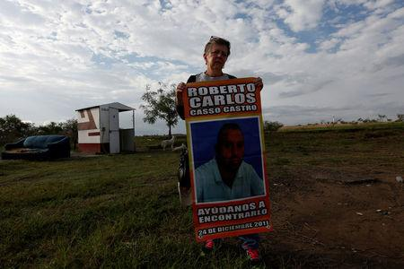 "Rosalia Castro holds a poster with a picture of her missing son, Roberto Casso, as she stands by the gate to a plot of land where skulls were found at unmarked graves, on the outskirts of of Veracruz, Mexico March 16, 2017. The poster reads: ""Help us find him. December 24, 2011."" REUTERS/Carlos Jasso"