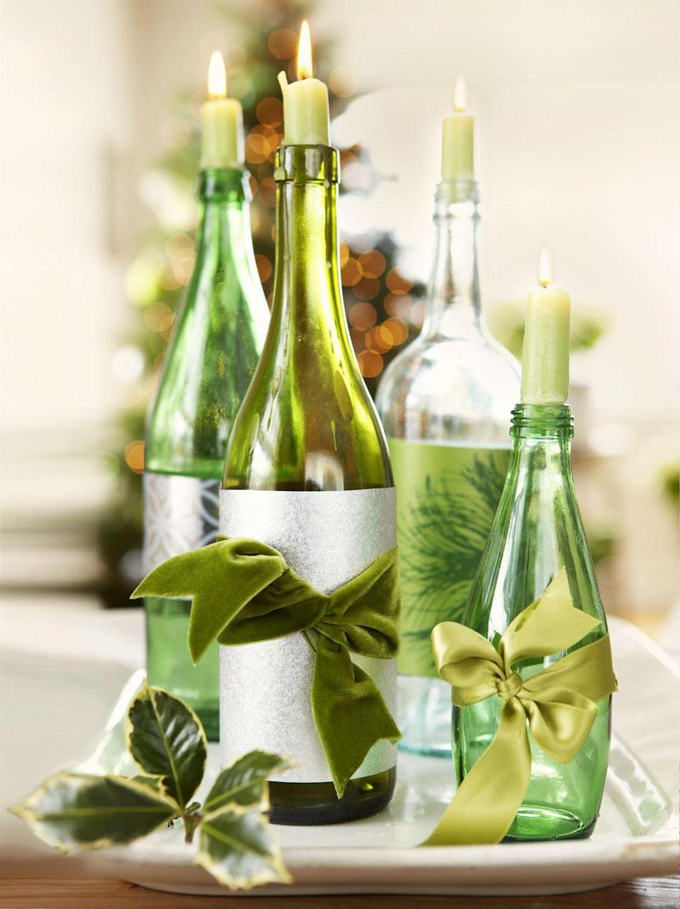 """<p>Empty bottles become holiday-ready candleholders with some silvery wrapping paper and lush green ribbons.</p><p><a class=""""link rapid-noclick-resp"""" href=""""https://www.amazon.com/Colonial-Candle-Classic-Willow-Green/dp/B0085F24CE?tag=syn-yahoo-20&ascsubtag=%5Bartid%7C10055.g.2196%5Bsrc%7Cyahoo-us"""" rel=""""nofollow noopener"""" target=""""_blank"""" data-ylk=""""slk:SHOP GREEN CANDLES"""">SHOP GREEN CANDLES</a></p>"""