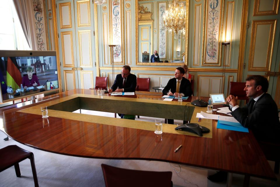 """French President Emmanuel Macron (R) listens to German Chancellor Angela Merkel during a video conference to discuss a joint plan to spur the EU's recovery from the coronavirus crisis at the Elysee Palace on May 18, 2020, in Paris. - The talks were held to """"define a French-German initiative to respond to the COVID-19 crisis at the European level, in the areas of health, the economic recovery, the environmental and digital transition, and industrial sovereignty,"""" French presidency said. (Photo by Francois Mori / POOL / AFP) (Photo by FRANCOIS MORI/POOL/AFP via Getty Images)"""